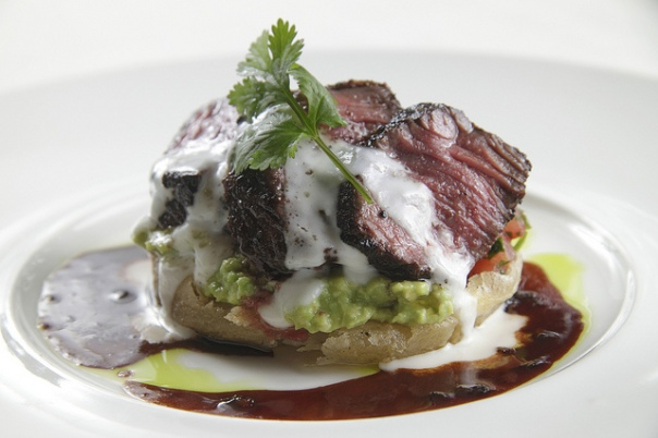 Cumin-Cured Creekstone Hanger Steak with Green Chile Redeye Gravy, Spicy California Avocado Sope and Queso Creama.